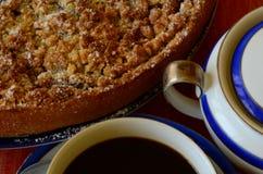 Tarta de la migaja del ciruelo con la taza de cuenco del café y de azúcar en fondo rojo Imágenes de archivo libres de regalías