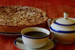 Tarta de la migaja del ciruelo con la taza de cuenco del café y de azúcar en fondo rojo Fotografía de archivo libre de regalías