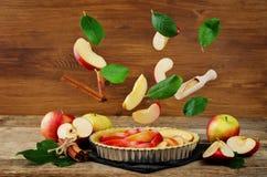 Tarta de manzanas con los ingredientes del vuelo para cocerla Foto de archivo libre de regalías