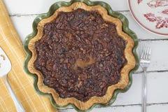 Tarta de nueces de la pacana de la calabaza cocida en un plato de cerámica verde Imagen de archivo libre de regalías
