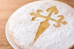 Tarta de Santiago. Traditional almond cake from Santiago in Spain on wooden table. Close up royalty free stock photo