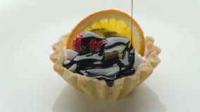 Tarta hecha en casa fresca de la fruta con la salsa de la fresa, de la naranja, del kiwi y de chocolate metrajes