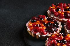 Tarta z jagodami zamyka w górę ciemnego tła na zdjęcia royalty free