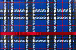 Tartan background with red ribbon and small bow. Gift box with Tartan background, red ribbon and small bow Stock Photos