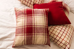 Tartan pillows on bed. Closeup of red cushions on bed Royalty Free Stock Photos