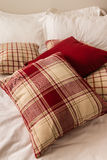 Tartan pillows on bed in hotel room. Collection of tartan pillows on bed in hotel room Stock Image