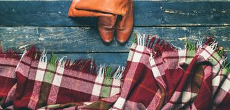 Tartan plaid red boots black old wooden planks. Tartan plaid and red boots on black old vintage wooden planks top view background long banner Royalty Free Stock Image