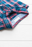 Tartan or Plaid shirt. On white wooden background Royalty Free Stock Photo