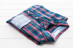 Tartan or Plaid shirt. On white wooden background Royalty Free Stock Images