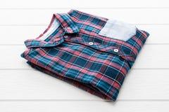 Tartan or Plaid shirt. On white wooden background Royalty Free Stock Photos