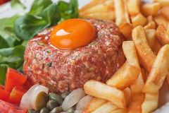 Tartar steak. Raw meat steak with egg yolk, onion and french fries Royalty Free Stock Images