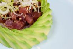 Tartare мяса голубого тунца на кровати риса, гарнированной с кусками авокадоа и тонкими кусками лук-пореев, черно-белый сезам стоковое изображение rf