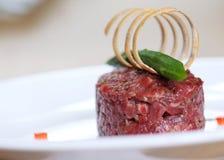 Tartare Bestandteile: Rohe Rindfleischfleischsalzpfefferknoblauchpaprika-Krautdekoration Stockfotografie