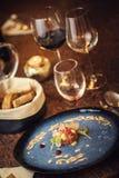 Tartare biff med ett exponeringsglas av vin och bålgetingar, produktfotografi för restaurangen, modern gastronomi royaltyfria bilder