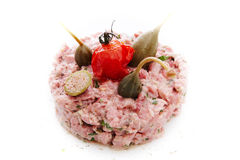 Tartare of cooked beef in its own juice with capers and tuna sau. Ce on white background deliciously Stock Photos