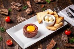 Tartare da carne crua da carne com especiarias e molhos diferentes separadamente para misturar Um vidro do vinho tinto na tabela  imagem de stock