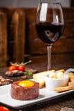 Tartare da carne crua da carne com especiarias e molhos diferentes separadamente para misturar Um vidro do vinho tinto na tabela  imagem de stock royalty free