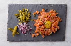 Tartare de color salmón con la yema de huevo, el pepino conservado en vinagre y las cebollas frescas Fotos de archivo libres de regalías