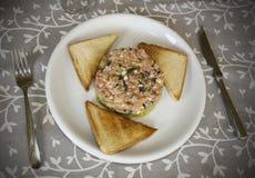 Tartare de color salmón con pan tostado en mantel Foto de archivo