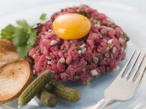 Tartare di bistecca con Cornichons, i crostini e un uovo Immagine Stock Libera da Diritti