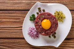 Tartare with egg, capers and cucumbers close-up top view. Beef tartare with egg, capers and cucumbers close-up on the table. horizontal top view Royalty Free Stock Photos
