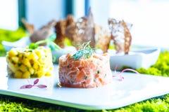 Tartare of fresh salmon. Lying on a white flat plate Stock Photos
