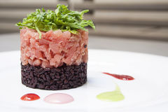 Tartare Gourmet. With black rise and rocket, red sauce decoration Royalty Free Stock Photo