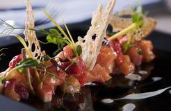 Tartare saumoné délicieux avec le souce de fraises, de pain grillé et de crème, plat noir, vue étroite d'angle images stock