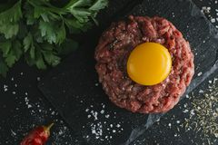 Tartare steak. Beef raw chopped meat with spices, herbs and egg yolk. Fresh, spicy, delicious, gourmet meal on dark Stock Photography