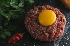 Tartare steak. Beef raw chopped meat with spices, herbs and egg yolk. Fresh, spicy, delicious, gourmet meal on dark Royalty Free Stock Photos