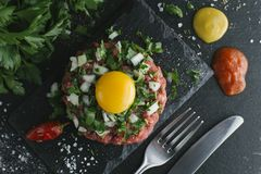 Tartare steak. Beef raw chopped meat with spices, herbs and egg yolk. Fresh, spicy, delicious, gourmet meal on dark Stock Photos