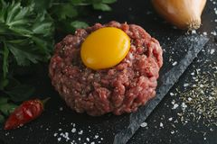 Tartare steak. Beef raw chopped meat with spices, herbs and egg yolk. Fresh, spicy, delicious, gourmet meal on dark Stock Images