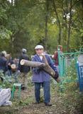 Tartaristán, Rusia - 25 de agosto de 2018 - un viejo hombre que lleva un palillo enorme del árbol aserrado en un bosque imagen de archivo