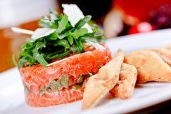 Tartaro di color salmone con i capperi, la rucola insalata ed il parmigiano immagine stock