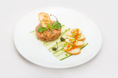 Tartaro di color salmone su un piatto bianco con le foglie verdi fotografie stock