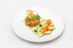 Tartaro di color salmone su un piatto bianco con le foglie verdi immagine stock libera da diritti