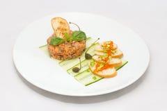 Tartaro di color salmone su un piatto bianco con le foglie verdi immagini stock