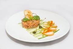 Tartaro di color salmone su un piatto bianco con le foglie verdi fotografia stock libera da diritti