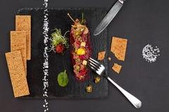 Tartaro fresco del manzo con sale ed erbe e pane croccante, colpo dello studio Tartaro della carne su scisto nero Su fondo bianco Fotografie Stock