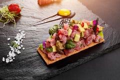 Tartaro fresco del tonno con sale e le erbe, colpo dello studio Tartaro del pesce su scisto nero Fotografia Stock