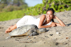 Tartaruga e mulher que encontram-se na praia, ilha grande Havaí Foto de Stock
