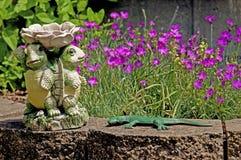 Tartarughe ceramiche, piccoli fiori porpora e geico verde Fotografie Stock