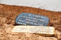 Tartarughe che intercalano segnale di pericolo sulla spiaggia Fotografia Stock