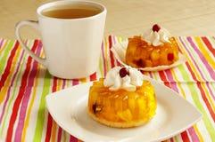 Tartas con crema azotada y una taza de té Fotografía de archivo libre de regalías