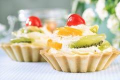 Tartas con crema de la fruta y de la vainilla con la cereza y el kiwi foto de archivo libre de regalías
