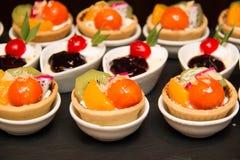 Tartas del postre de la fruta con crema, el kiwi, y la papaya Fotos de archivo