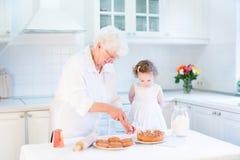 Tarte aux pommes affectueuse de cuisson de grand-mère avec la fille d'enfant en bas âge Images libres de droits
