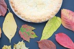 Tarte aux pommes avec des feuilles ou des feuilles d'automne avec l'au sol de dos de noir Image libre de droits