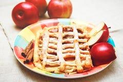 Tarte aux pommes avec la grille de pâtisserie, Sugar Pouder, du plat en céramique avec de la cannelle et Apple frais, modifiés la Photo stock