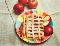 Tarte aux pommes avec la grille de pâtisserie, Sugar Pouder, du plat en céramique avec de la cannelle et des morceaux d'Aple frai Photos stock